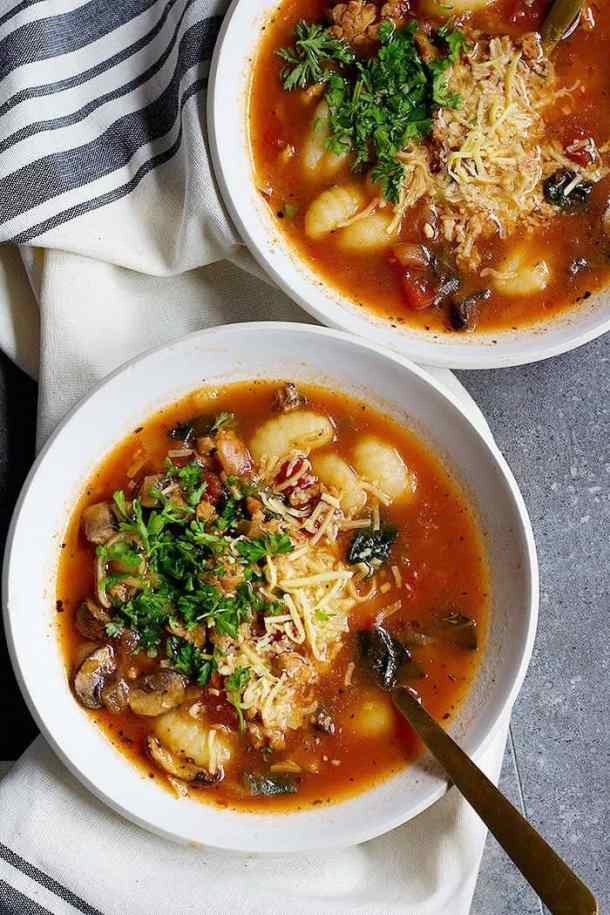 Bowls of Sausage Soup with gnocchi topped with Parmesan cheese.