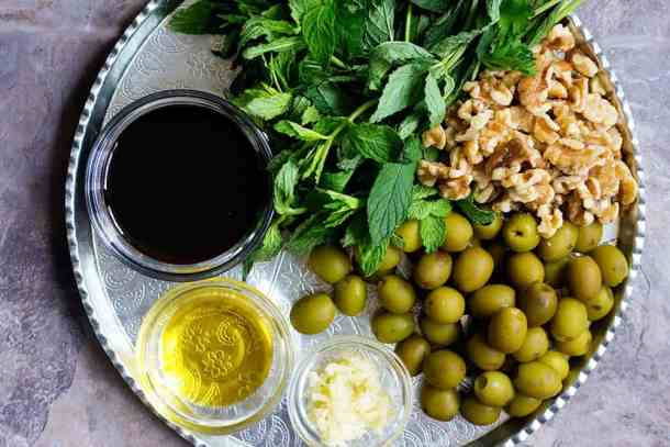 To make marinated olives. you need olives, walnuts, pomegranate molasses, garlic, extra virgin olive oil and mint.