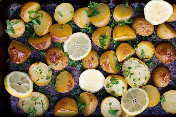 Greek style potatoes are roasted in the oven and served with lemons