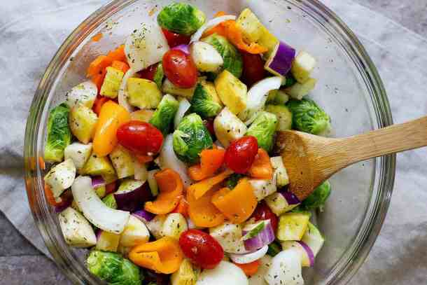 Chop all the vegetables and mix them with olive oil and spices in a large bowl.