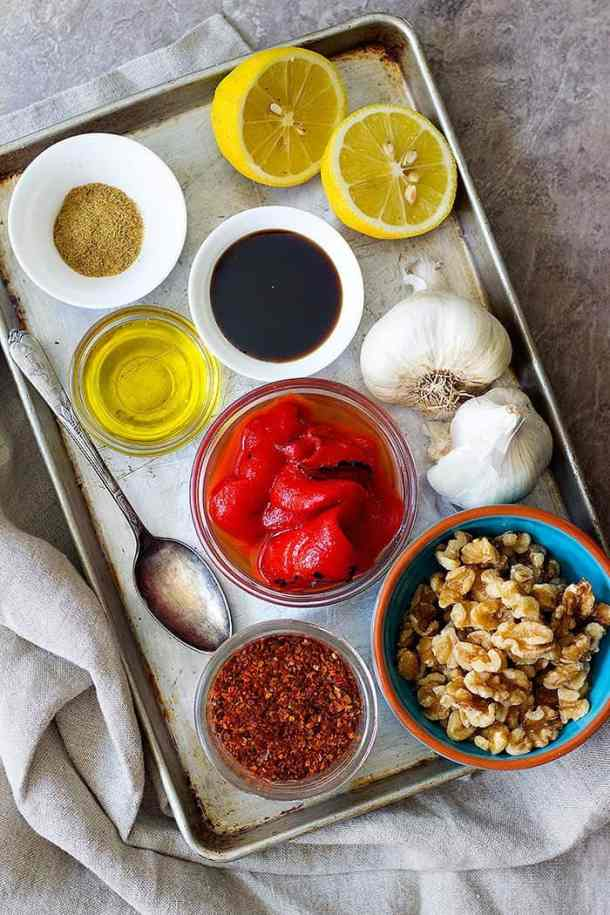 Muhammara ingredients are roasted red pepper, lemon, walnuts, pomegranate molasses, Aleppo pepper, olive oil and cumin and garlic