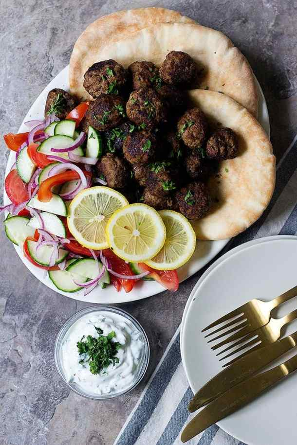 Serve Greek lamb meatballs with pitas and vegetables.