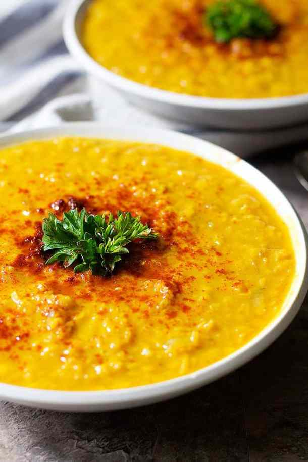 This turmeric red lentil soup is topped with paprika and parsley.