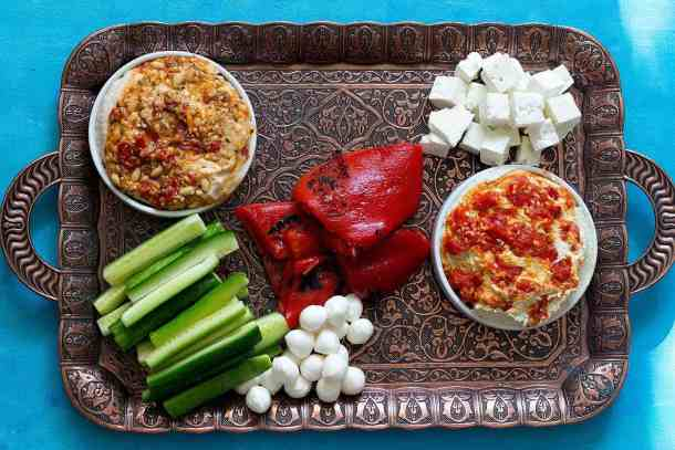 Place hummus, cucumber and cheese on the Greek mezze platter.