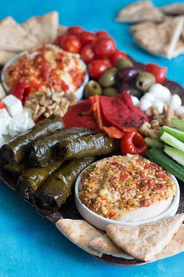 A Mediterranean platter includes hummus, roasted peppers, dolmas and cucumbers.