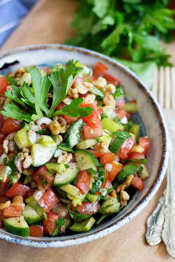 a bowl of Turkish tomato salad with cucumbers and walnuts.