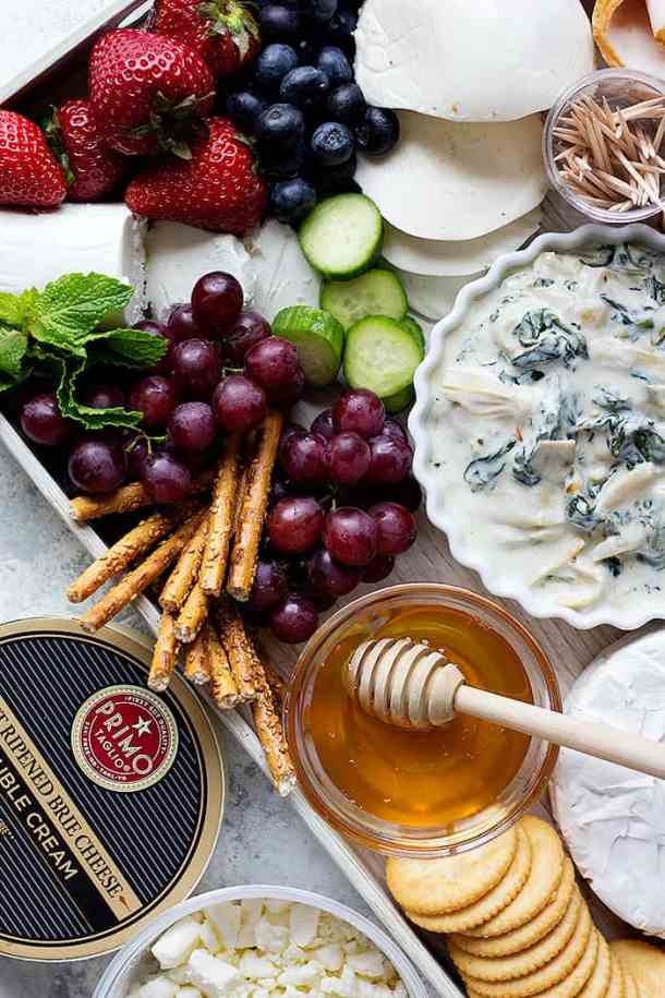 grapes, strawberries and cheese served with a cold spinach dip on a board