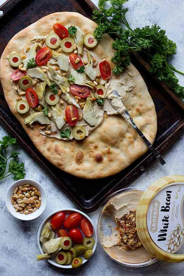 Top the flatbread with hummus, olives and tomatoes.
