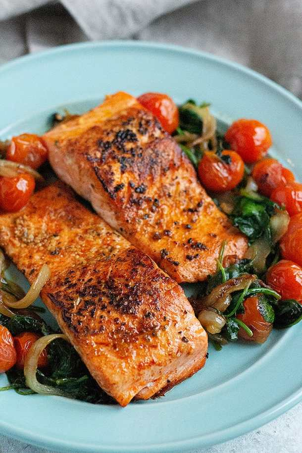 two seared salmon fillets on a plate with cooked spinach and tomatoes.