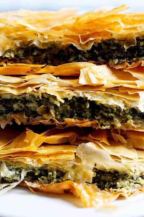 Have you every tried spanakopita? Spanakopita is a classic Greek pie made with phyllo dough, spinach and feta. It's packed with so much flavor and one slice is never enough! Learn how to make spanakopita recipe with a video tutorial.