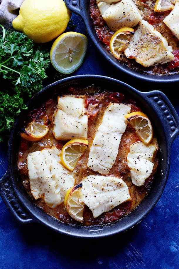 white fish fillets cooked in a tomato pepper sauce in an oven safe pan.