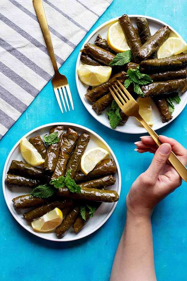 Two plates of dolmas with lemon and mint.