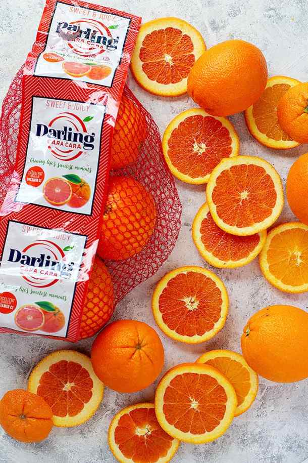 cara cara oranges sliced next to the packaging.