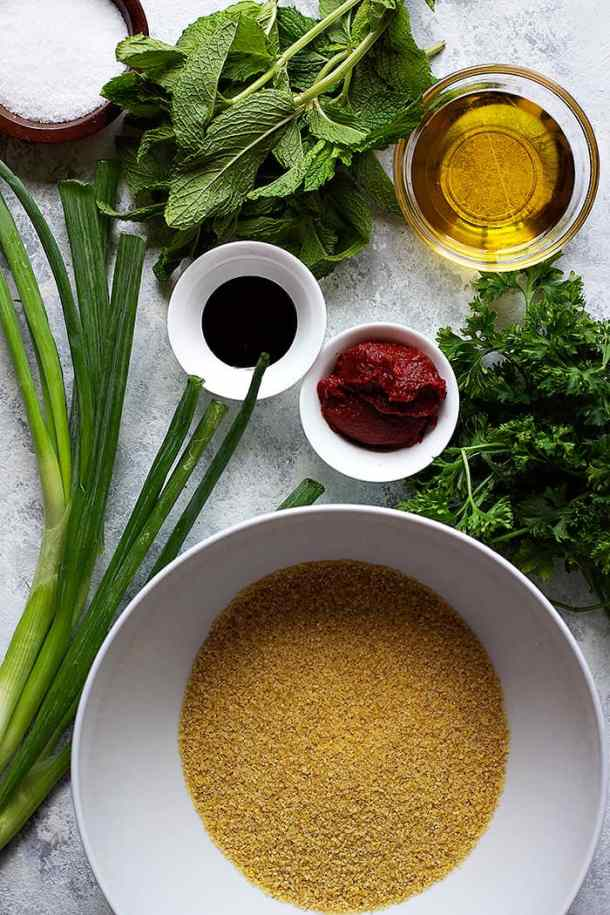 to make Turkish bulgur salad kisir your need bulgur, green onions, parsley and mint. You also need tomato paste, pomegranate molasses and olive oil .