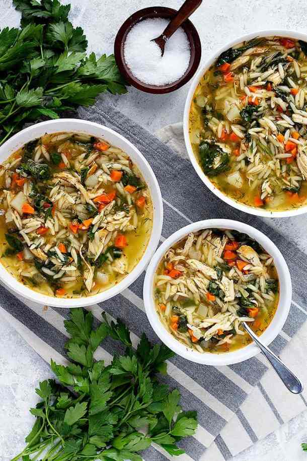 Three white bowls of soup. This is the chicken soup made with orzo and spinach.
