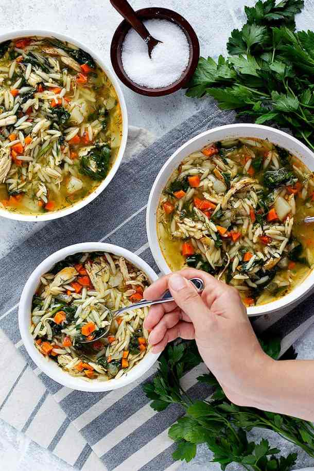 Three bowls of lemon orzo soup with chicken and spinach.