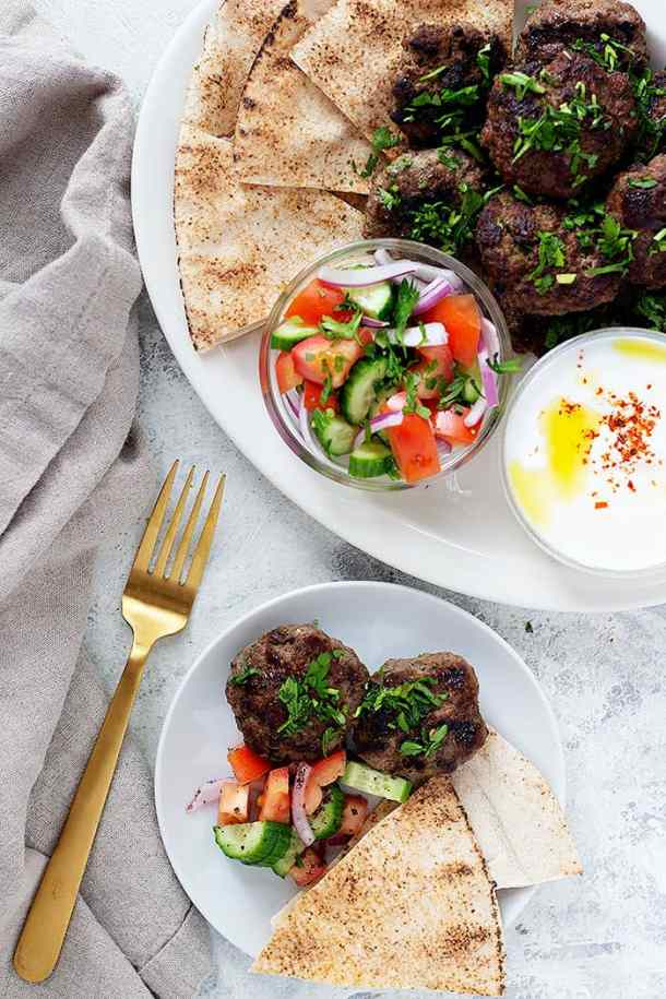 Tow plates of kofte kabobs with cucumbers tomatoes and yogurt sauce and pita bread.