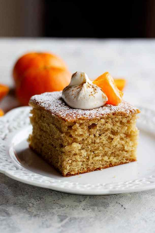 A slice of ginger spice cake topped with whipped cream and a clementine