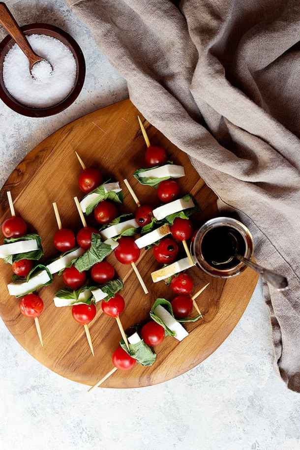 Caprese skewers on a wooden board with some salt and balsamic vinaigrette.