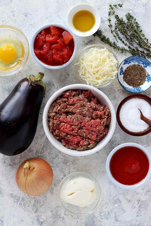 To make this recipe we need eggplant, onion, ground beef, tomatoes, egg, cheese, olive oil and spices.