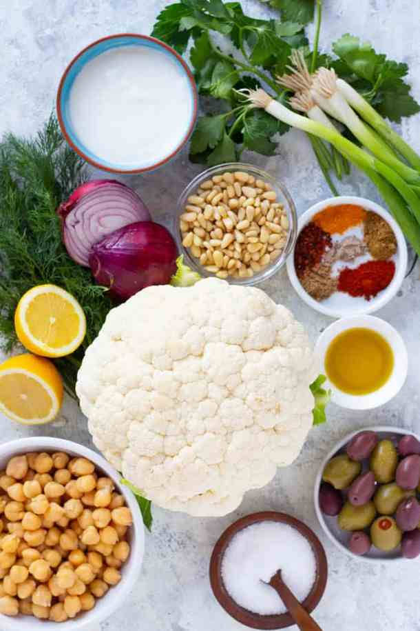 To make this salad you need cauliflower, spices, chickpeas, olives, olive oil, pine nuts, red onion, lemon, yogurt and herbs.