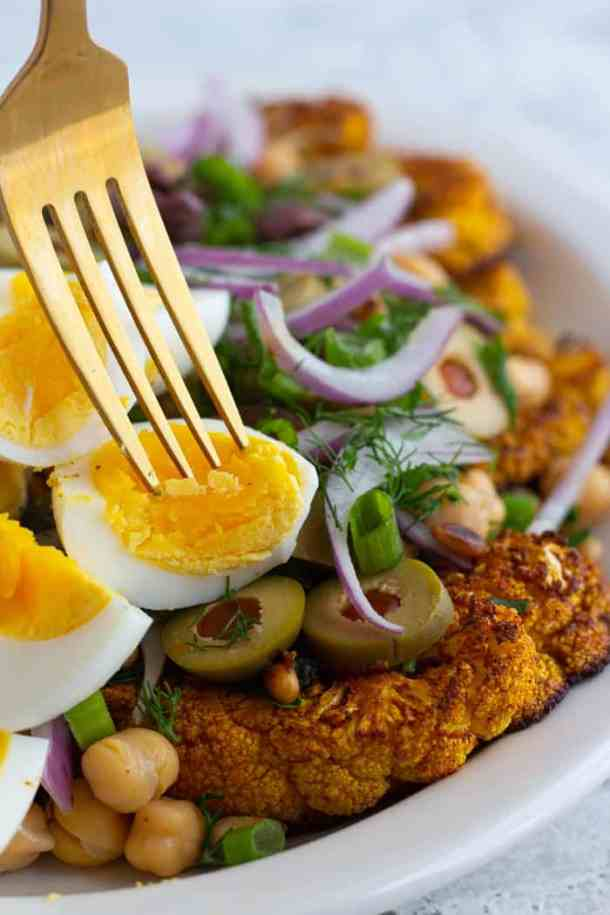 Top the salad with olives, onions and hard boiled eggs.