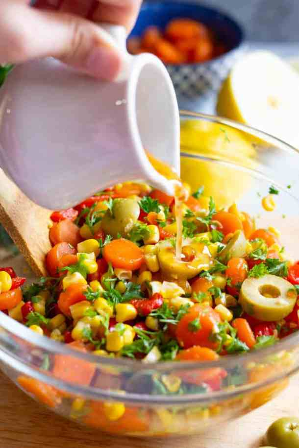 The dressing for this Mediterranean corn salad is made with olive oil, lemon juice, aleppo pepper and salt.