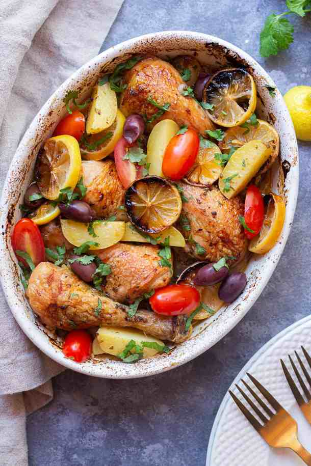 Greek Chicken and potatoes in a baking dish topped with tomatoes and olives.