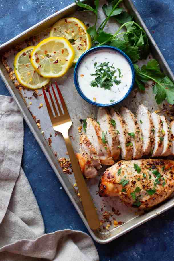 A tray with baked Greek chicken sliced and topped with parsley.