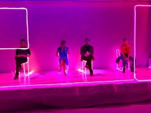 """Skuespillere sitter i et rosa neonbelyst """"rom"""" på scenen."""