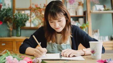 content asian woman writing in copybook in floral shop