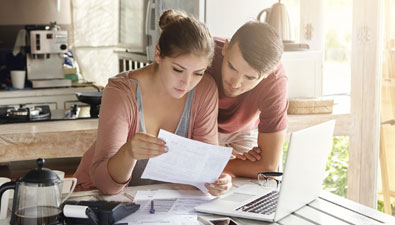 man and woman looking through finances