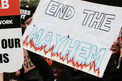 """NO MORE AUSTERITY demonstrator holding """"END THE MAYHEM"""" placard at Piccadilly Gardens, Manchester. 1st October 2017."""