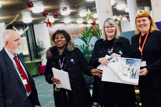 Photograph of Councillor David Norman MBE, UNISON members and Councillor Helen McDonald hold a Christmas card signed by the people of Southend demanding an end to Scrooge-like pay rises.
