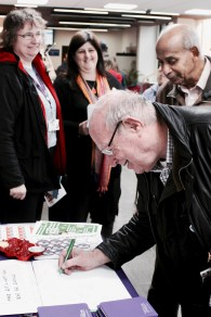 Photograph of Pay Up Now! supporter signing Christmas card to local councillors demanding an end to Scrooge-like pay rises at a protest at the Civic Centre, Southend Borough Council.