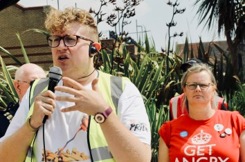 Photograph of Dan Turpin (Southend Pride Organiser) addressing Parade at the Royal Plaza, Southend-on-Sea. Claire Wormald (Secretary, UNISON Southend-on-Sea) in the background.