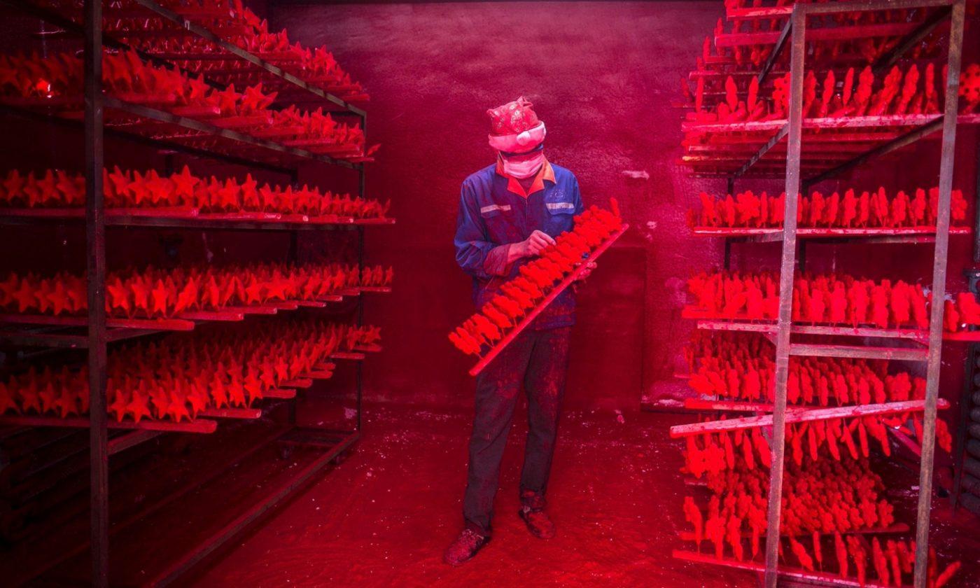 Dos hombre producen cerca de 5.000 gorros de Papá Noel cada día por unos 385 euros al mes. Foto: China Daily/Reuters