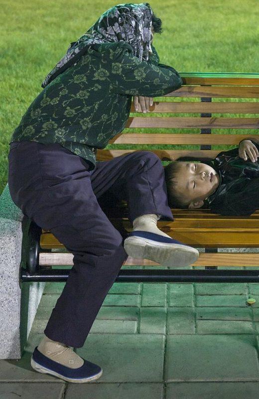 """""""La paranoia está fuertemente instalada en las mentes norcoreanas. Tomé esta foto en un parque de atracciones, una madre y su hijo descansando sobre un banco. Me pidieron que borrase la imagen ya que los guías estaban seguros de que diría que estas personas son gente sin hogar"""" Eric Lafforgue."""