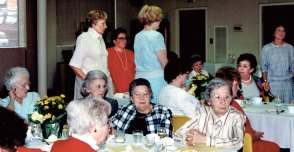 From left: (seated, facing camera) Carolyn Gurman (in blue top), Beatzy Becker, Janet Henry (plaid jacket), Dora Miles (striped top). (Seated, back to camera, in red) Sara Fine. (Standing) Anne Gurman (at left in white), unidentified (in red), Laurel Fischbaum (in blue), Sunny Cohen (at far right, in blue). (Seated) unidentified (in white, back to camera), Eva Kor (at right, in red), Pat Hoffman (at left rear), Estelle Corrigan (in necklace, across from Eva).
