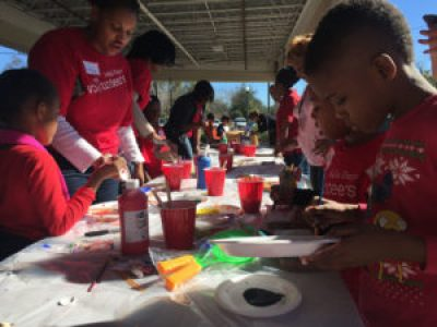 "Volunteers work on painting ""peace tiles"" to help beautify a community center."