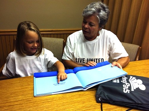 Hailey Reeder, now a rising first  grader, practices reading with her ReadingPals volunteer, Phyllis.