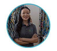 IT student stands among many colorful wires and stacks of hardware in a server room