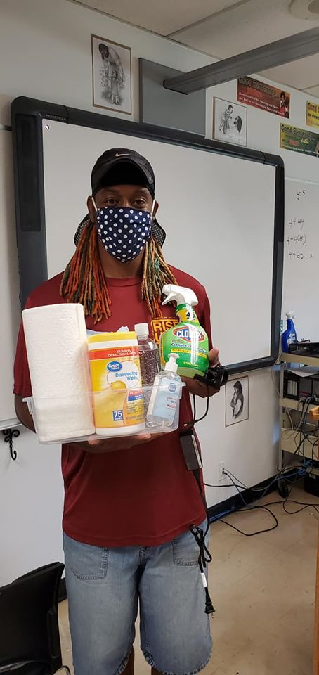 Person wearing mask and holding cleaning supplies