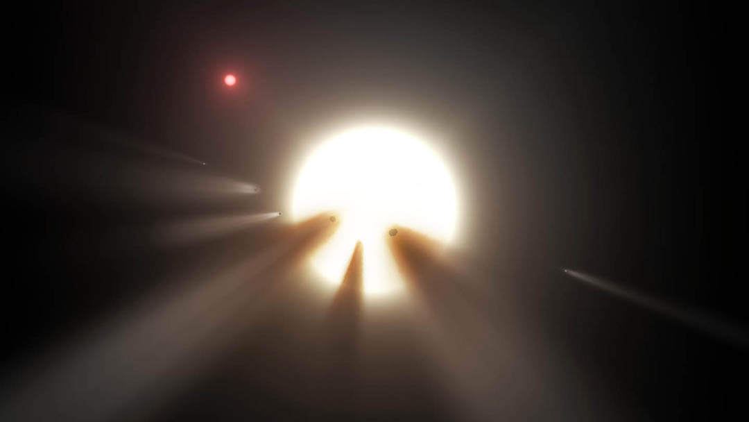 Artist's impression of an orbiting swarm of dusty comet fragments around Tabby's Star. Could these be responsible for its peculiar dips in brightness or is there a biological reason? A small red dwarf star (above, left) lies near Tabby's. Credit: NASA/JPL-Caltech