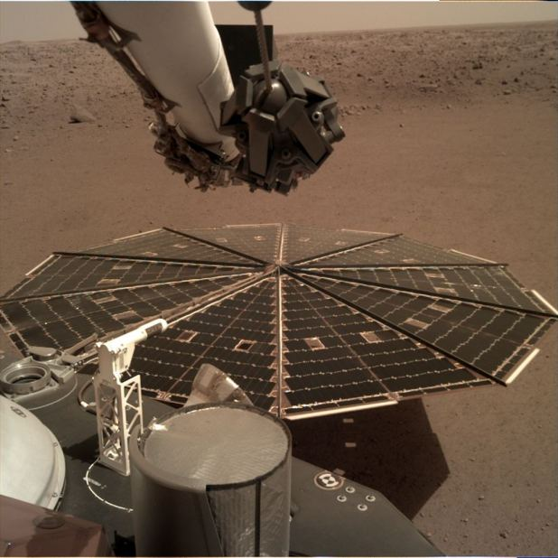 One of Mars Insight's 7-foot (2.2-meter) wide solar panels is fixed in the elbow of his robotic arm by Landers' instrument deployment camera.  Dust accumulated on the panels has reduced the power available for the mission.  Credits: NASA / JPL-Caltech
