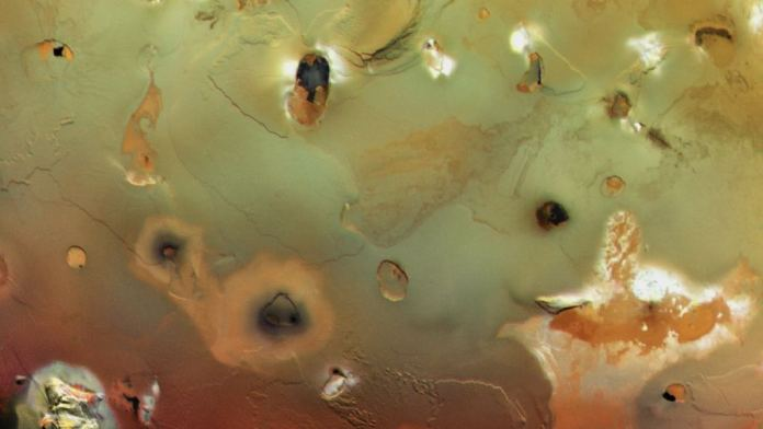 The surface of Io is covered with dark, collapsed volcanoes. Image Credit:  NASA/JPL/USGS
