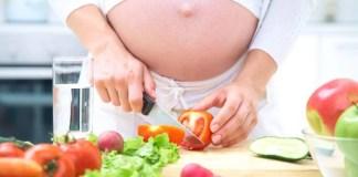 Donna incinta che taglia le verdure in cucina