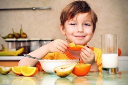 Bambino sorridente mangia soddisfatto frutta e yoghurt