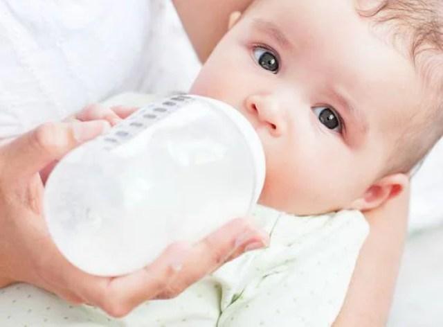 Bambino pochi mesi mentre viene allattato con biberon