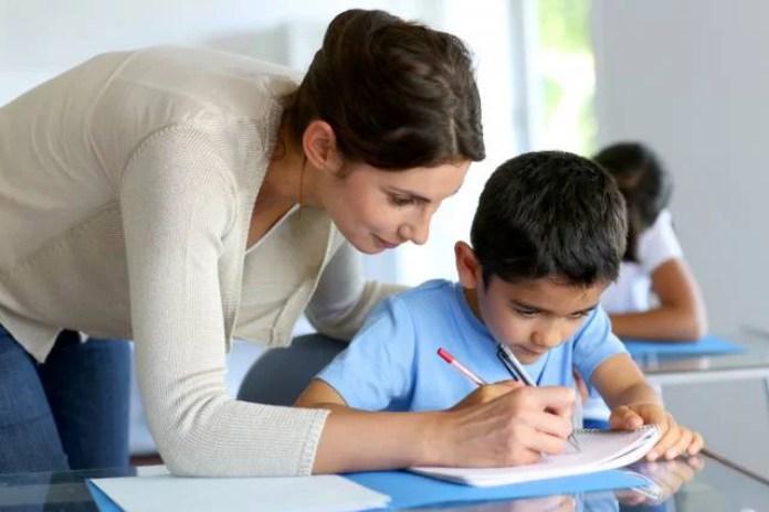 Una maestra spiega a un bambino